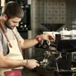 Young barista making coffee on the espresso machine