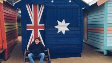 Ignacio seated in front of a cabin which has a painted Australian flag