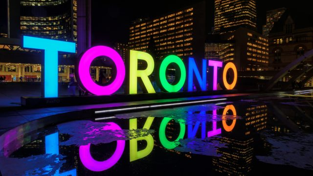 View of Toronto Sign on Nathan Phillips Square at night, in Toronto, Canada. Illuminated City Hall and the Freedom Arches in background.