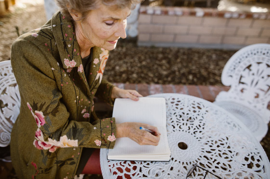 Elderly woman sitting outdoors and writing in a notebook