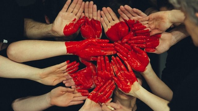many hands together with red heart - student mental health